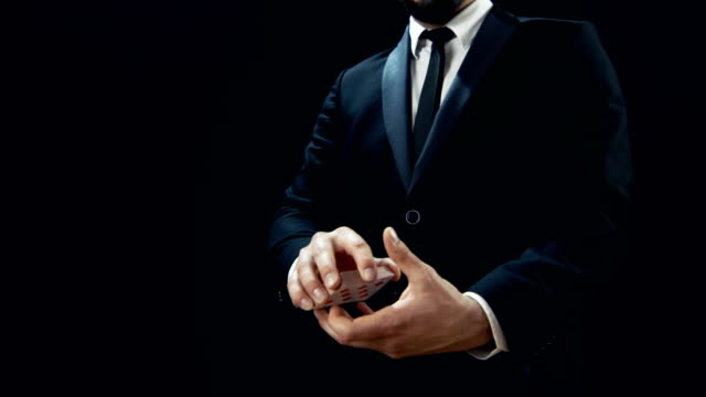 Close-up of a Magician's Hands Performing Card Trick. Throwing and Catching Cards in the Air. Background is Black. Slow Motion. video
