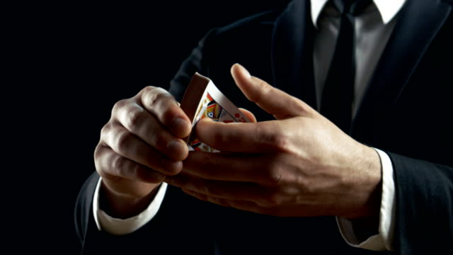 Close-up of a Magician's Hands Performing Card Trick. Throwing and Catching Cards in the Air. Background is Black. Slow Motion.