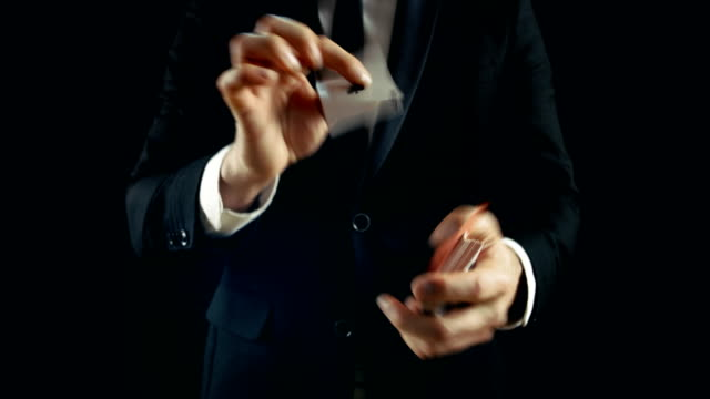 Close-up of a Magician's Hands Performing Card Tricks and Showing His Skills. Magician Wears Black Suit and is Shot on Black Background. video