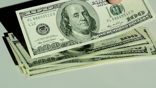 Closeup of a Male Hands Counting Hundred Dollar Bills at a Table video
