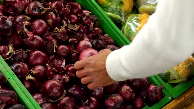 Close-up of a man chooses red onions in a supermarket. Slow motion.