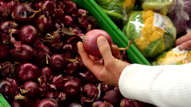 Close-up of a man chooses red onions in a supermarket. Slow motion. Close-up of a man chooses red onions in a supermarket. The family buys food and vegetables at the grocery store. Slow motion. red onions stock videos & royalty-free footage