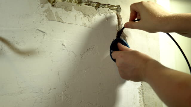 Close-up of a man installing an electrical outlet. video