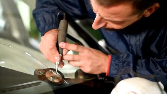 vidéos et rushes de gros plan d'un homme professionnellement à l'atelier engagé dans l'élimination des fissures sur le pare-brise de la voiture. - pare brise