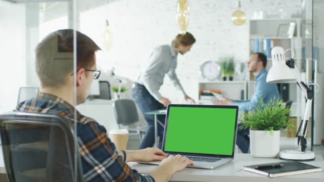 vídeos de stock e filmes b-roll de close-up of a man sitting at his desk with green screen laptop. in background blurred and brightly lit office where two young man shake hands and sit down for conversation. - espaço vazio
