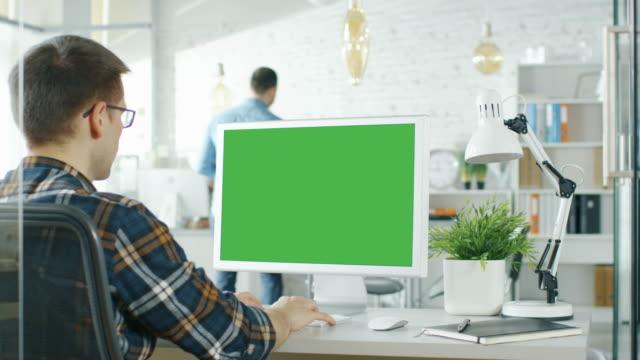 Nahaufnahme eines Mannes sitzt an seinem Schreibtisch mit Green-Screen-PC auf dem Tisch. Im Hintergrund unscharf und hell beleuchteten Büro dort, wo durch Office Routine machen. – Video