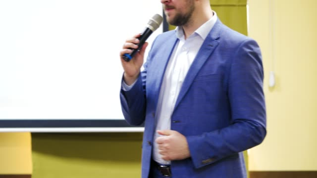 stockvideo's en b-roll-footage met close-up van een man speaker in blue jacket te praten in de microfoon. - lood