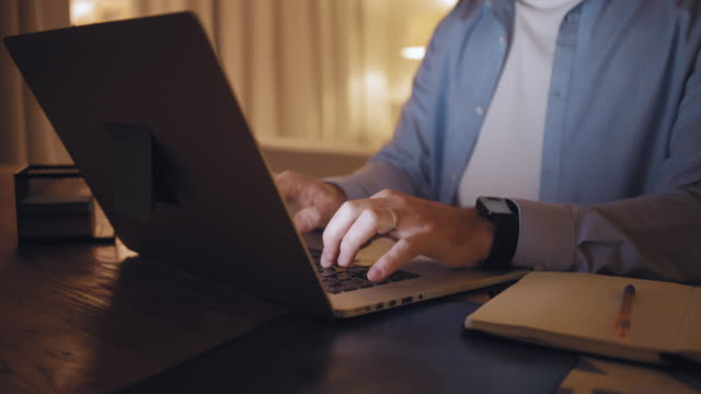 close-up of a man working from home typing on laptop till late night - usare il laptop video stock e b–roll