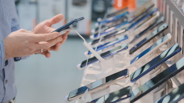 Closeup of a man's hand is choosing to buy a new smartphone near the storefront in an electronics store Closeup of a man's hand is choosing to buy a new smartphone near the storefront in an electronics store. electronics store stock videos & royalty-free footage