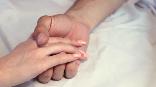 close-up of a mans hand lies on a white sheet - mano donna dita unite video stock e b–roll