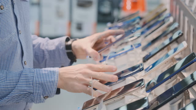 vídeos de stock e filmes b-roll de close-up of a man's hand rotates and inspects the design of a new smartphone in a modern electronics store. take the phone before buying - new