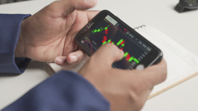 close-up of a man's hand trading stocks through a smartphone.