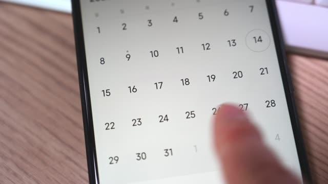 vídeos y material grabado en eventos de stock de primer plano de la mano de un hombre utilizando una aplicación de calendario de teléfono inteligente. - calendar