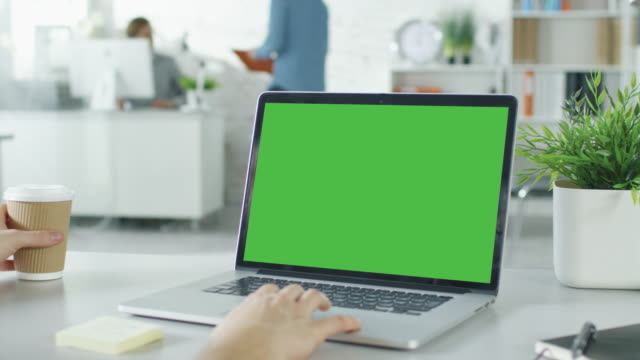 Video Close-up of a Man's Hands Working on Green Screen on a Laptop. In Background Blurred and Brightly Lit Office where One Man Approaches the Other and They Have Discussion.