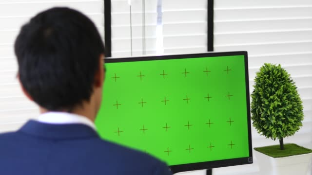 Close-up of a Man's Hands Working on Green Screen on a Laptop