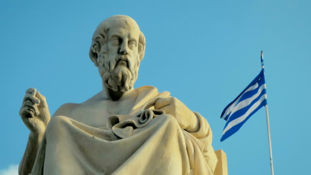 Close-up of a marble statue of the great Greek scholar of antiquity of Plato on background of the national flag of Greece. video