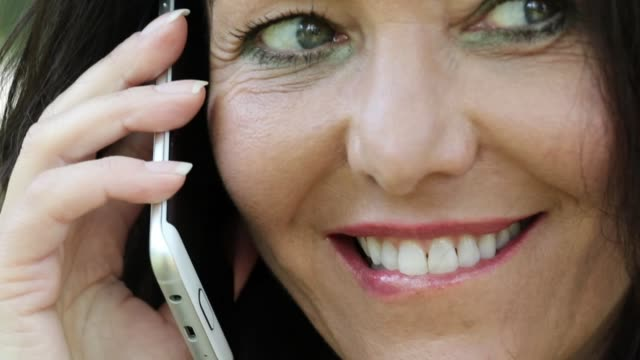 Close-up of a mature woman talking on the phone A close-up shot of a mature woman speaking on her mobile phone, relaxed, positive emotions. donna stock videos & royalty-free footage