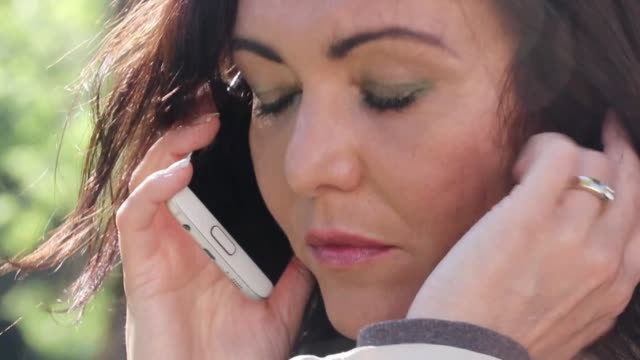 Close-up of a mature woman talking on the phone A close-up shot of a mature woman speaking on her mobile phone, looking sad. donna stock videos & royalty-free footage