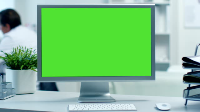 close-up of a monitor with green screen. doctor working at his desk in the background. shot in a modern medical office. - стол стоковые видео и кадры b-roll