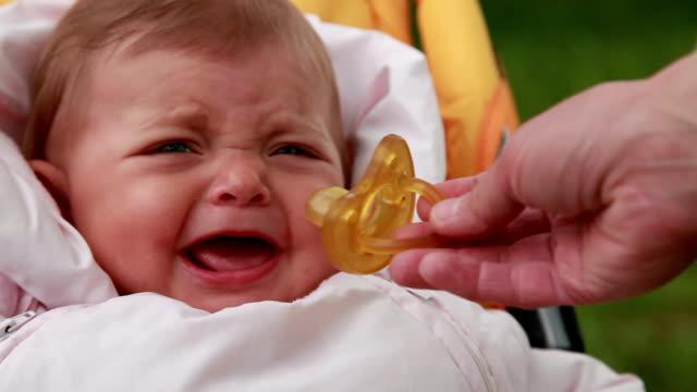 vídeos de stock, filmes e b-roll de close-up de uma mão de mães dando a chupeta para um bebê - bico