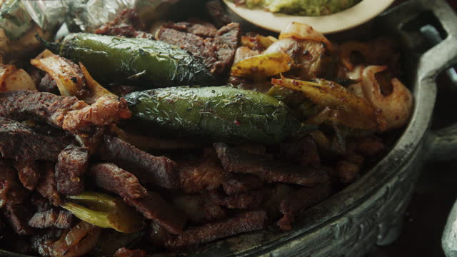 A Closeup Of A Mouthwatering Platter Of Beef Fajitas, With Sauteed Onion And Peppers Topped With Two Roasted Chili Peppers With A Side Of Guacamole, Limes And Hot Fresh Corn Tortillas
