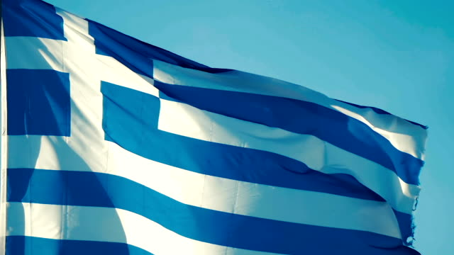 slow motion: close-up of a national greek flag flying in the wind of background a blue sky. - grecia stato video stock e b–roll