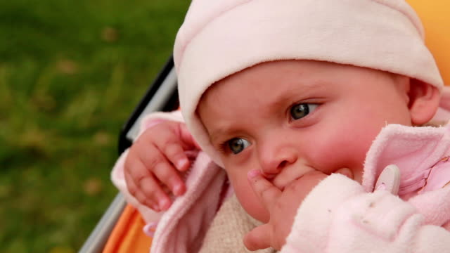 Close-up of a pensive baby sitting in the pram video
