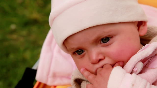 Close-up of a pensive baby sucking her fingers video