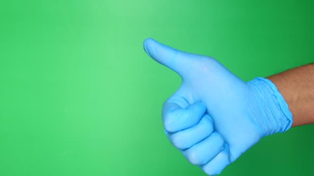 vídeos y material grabado en eventos de stock de primer plano de una persona en guantes médicos mostrando un pulgar hacia arriba. - guante quirúrgico