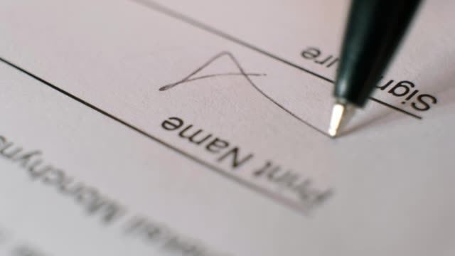 close-up of a person signing a business contract with a black ballpoint pen. - firma video stock e b–roll