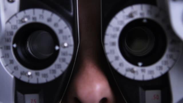 vidéos et rushes de gros plan d'un réfracteur lors d'un examen ophtalmologique - réfracteur