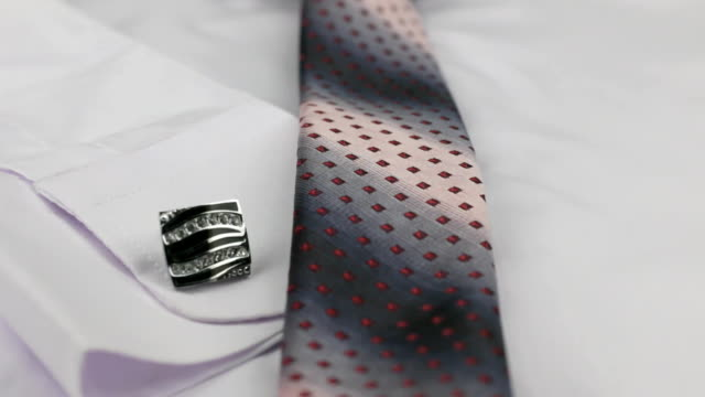 Close-up of a pink tie and cufflinks lying on a white shirt. Dolly shot. Close-up of a pink tie and cufflinks lying on a white shirt. Dolly shot. Fashionable subject video button down shirt stock videos & royalty-free footage