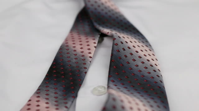 Close-up of a pink tie lying on a white shirt. Dolly shot. video