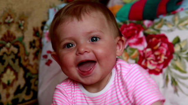 Close-up of a positive baby looking at camera video