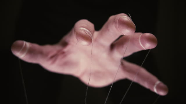 Closeup of a puppet hand with string tied around the fingers We are being manipulated concept. Large scary hands with puppet string tied around fingers marionette stock videos & royalty-free footage