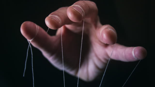 Closeup of a Puppet Master hand with string We are being manipulated concept. Large scary hands with puppet string tied around fingers marionette stock videos & royalty-free footage