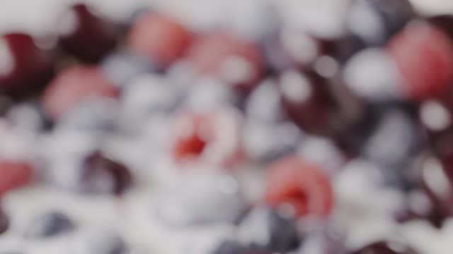 Close-up of a ripe juicy cherries, raspberries, blueberries with milk yogurt. Changing focus of berries background. Slow motion video in 4K. Soft focus.