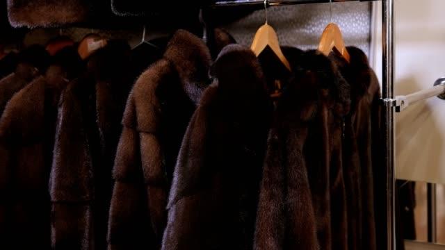 vídeos y material grabado en eventos de stock de primer plano de una fila de hermosos abrigos de visón de lujo en perchas en una tienda de ropa. - piel textil