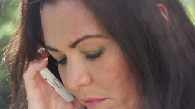 Close-up of a sad mature woman talking on the phone A close-up shot of a mature woman speaking on her mobile phone, looking sad. donna stock videos & royalty-free footage
