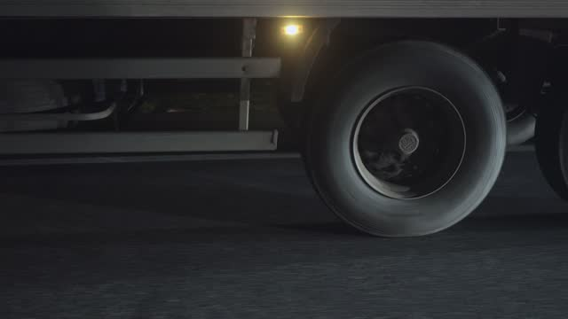 primo livello di una ruota semirimorchio in movimento in autostrada di notte. - truck tire video stock e b–roll