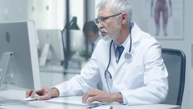 Nahaufnahme von einem Senior-Arzt und seinem Assistenten arbeiten bei Desktop-Computern. Sitzen in hell beleuchteten Büro. – Video