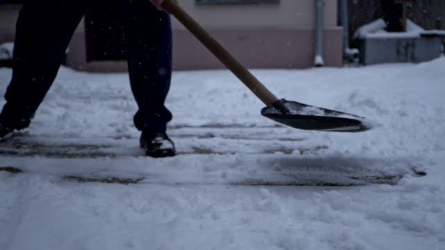 närbild av en ledande man skotta snön från sin bakgård - skyffel bildbanksvideor och videomaterial från bakom kulisserna