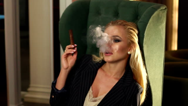 Close-up of a sexy woman Smoking a cigar in a bar in a cafe. Slow motion.