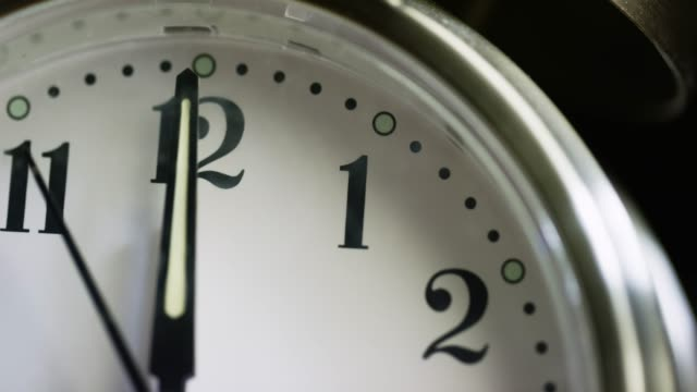 Close-Up of a Silver-Colored, Metal, Retro-Style, Analog Alarm Clock Almost Striking the Hour