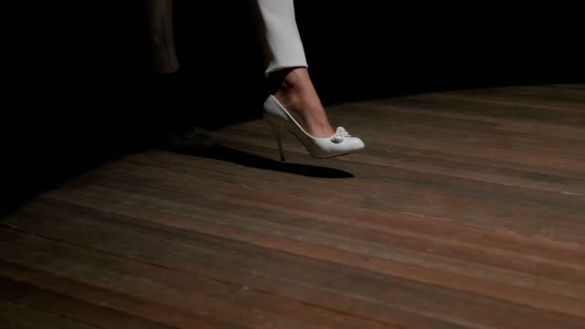 A close-up of a singer in white high-heeled shoes enters the stage in the dark.