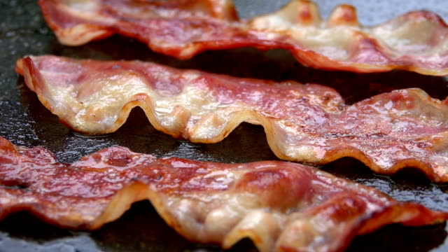 Close-up of a slice of bacon fried on grill video