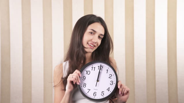 A close-up of a smiling happy girl. She twists a wall clock in her hands, it is noon. Midnight.