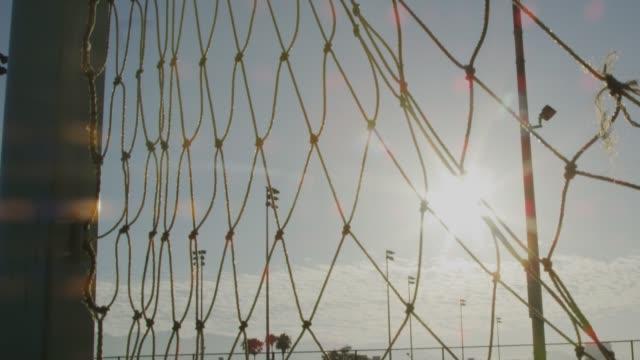 nahaufnahme eines fußballnetzes mit schönem sonnenlicht - netzgewebe stock-videos und b-roll-filmmaterial