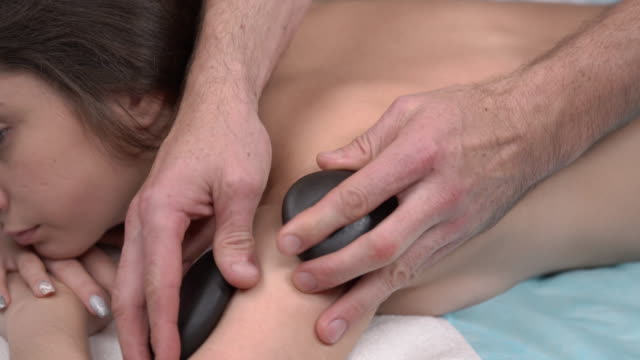 close-up of a sophisticated therapist performing back massage with stones. exotic massage. spa and wellness concept - terapia lastone filmów i materiałów b-roll