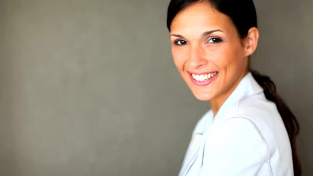 close-up di una donna contro sfondo grigio - sorriso aperto video stock e b–roll